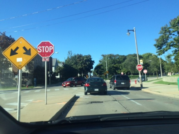 Photo of a traffic intersection with stop signs on both the right and left side of the street facing the driver.