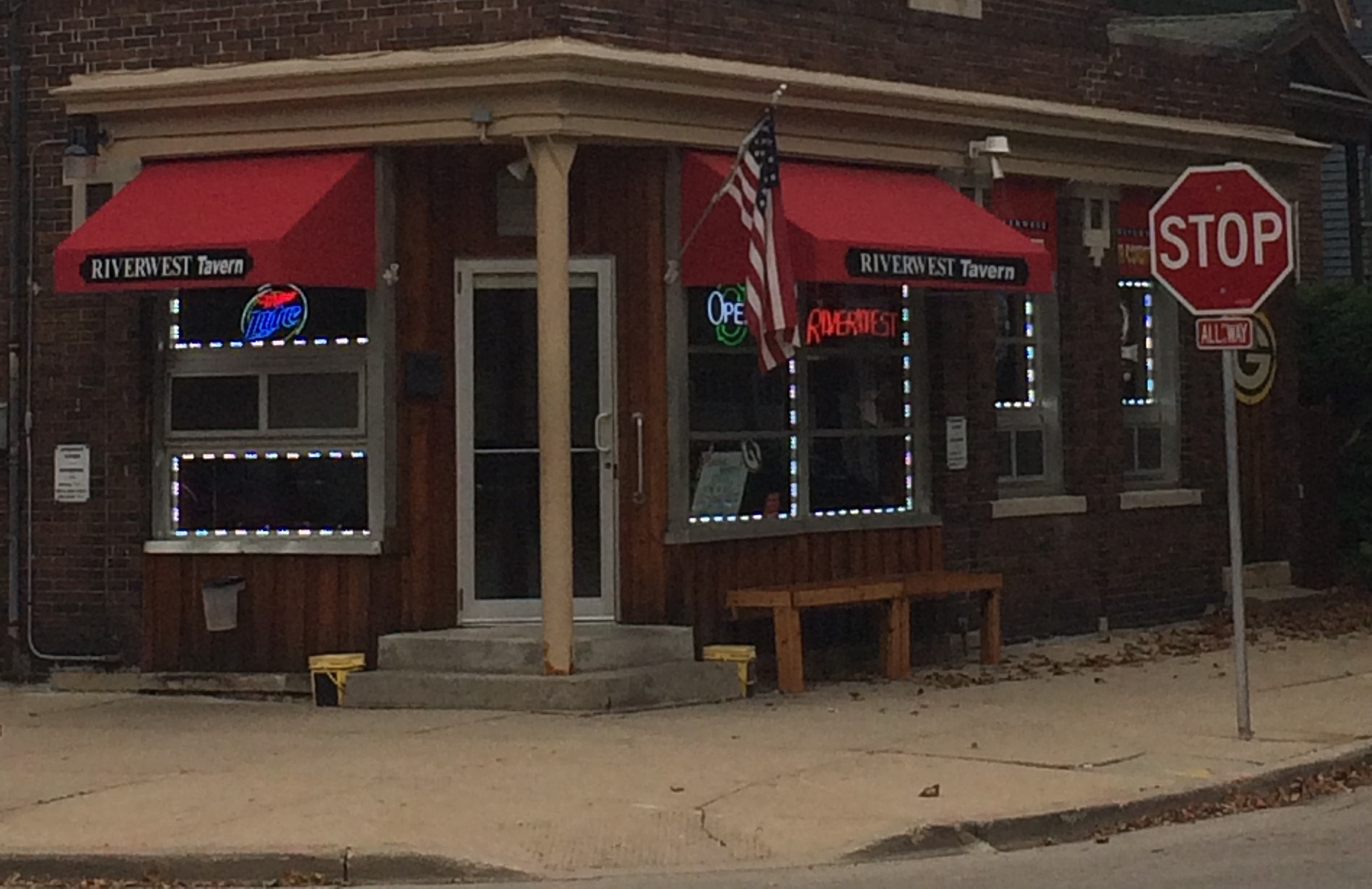 Picture of a bar with red awnings on the corner of an intersection.
