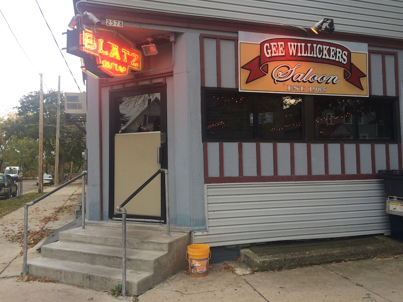 """Picture showing the facade of Gee Willickers Saloon, a bar on the corner of an intersection. A neon sign above the door reads, """"Blatz on Tap""""."""