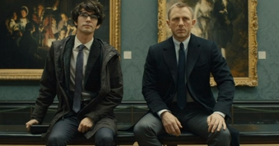 Movie still from Skyfall. Q (Ben Whishaw) on the right and James Bond (Daniel Craig) on the left. Both men are sitting on a bench in an art museum looking out at the camera. Behind them are paintings cinematically portraying Skyfall as Art.