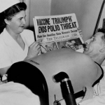 "Photo of nurse showing paper headline reading ""Polio Vaccine Discovered"" to man in iron lung machine."