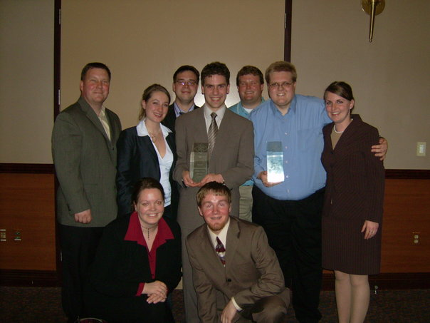 Photo of Minnesota State University, Mankato forensics team, including Matthew Collie, holding trophies.