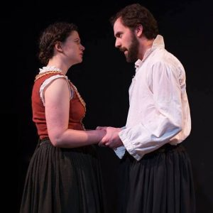 Production photo from Equivocation by Bill Cain. Judith (left) and Shag (right, played by Matthew Collie) hold hands. Photo by Kensie Wallner.