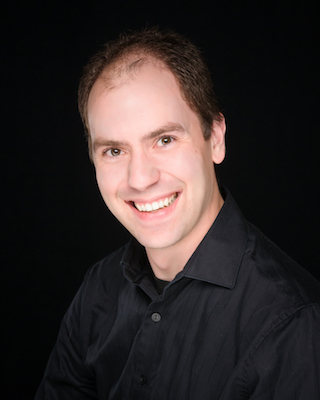 Photo of Matthew Collie in a black shirt smiling at the camera on a black background.