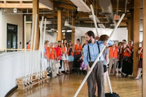 Photo of the interior of an art museum. Foreground: Matthew Collie faces camera standing back to back with a woman. Both are holding white PVC poles. Background: Crowd in orange vests watching. Photo by Kensie Wallner.
