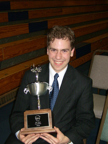 Photo of Matthew Collie seated, holding a forensics trophy.