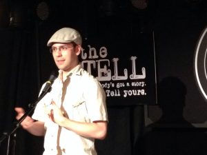 Photo of a Matthew Collie in a white shirt and cap talking into a microphone on a black background.