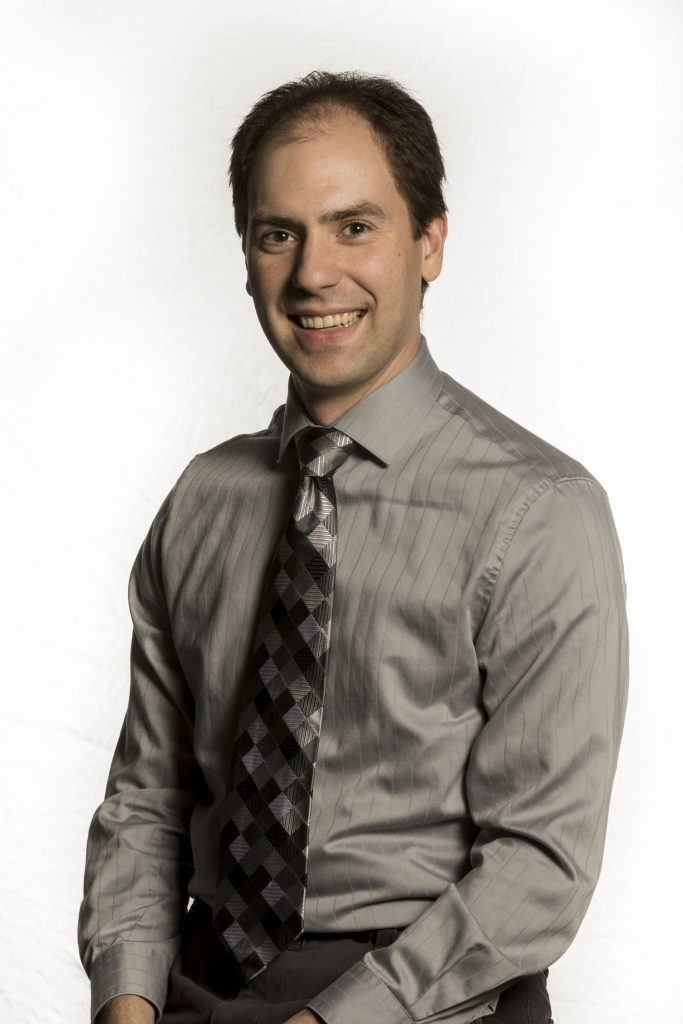 Photo of Matthew Collie smiling at the camera in a grey dress shirt and a grey and black tie.